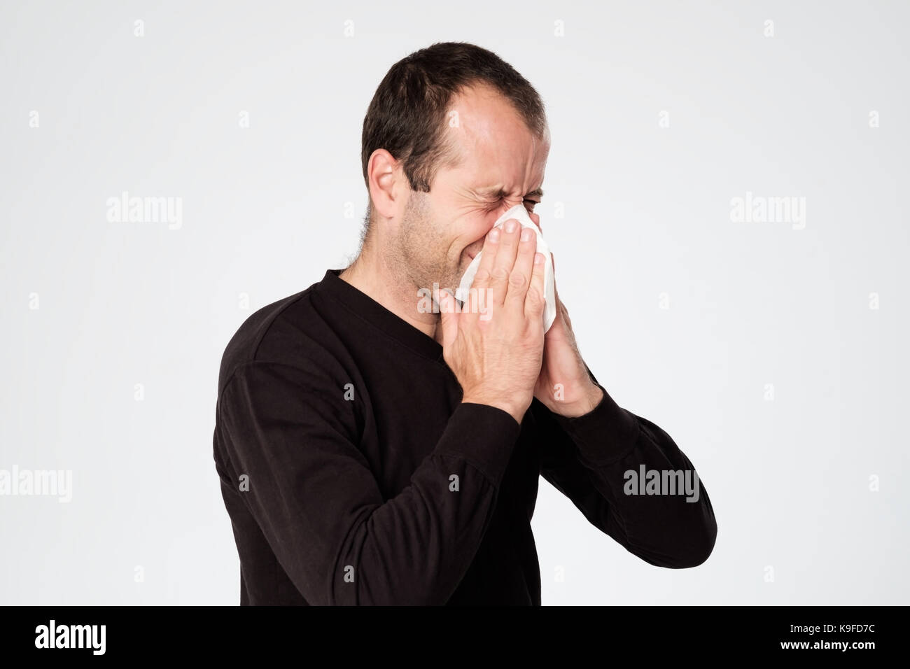 Mature man is ill from colds or pneumonia, sneezing in napkin. Suffering from flu virus. - Stock Image