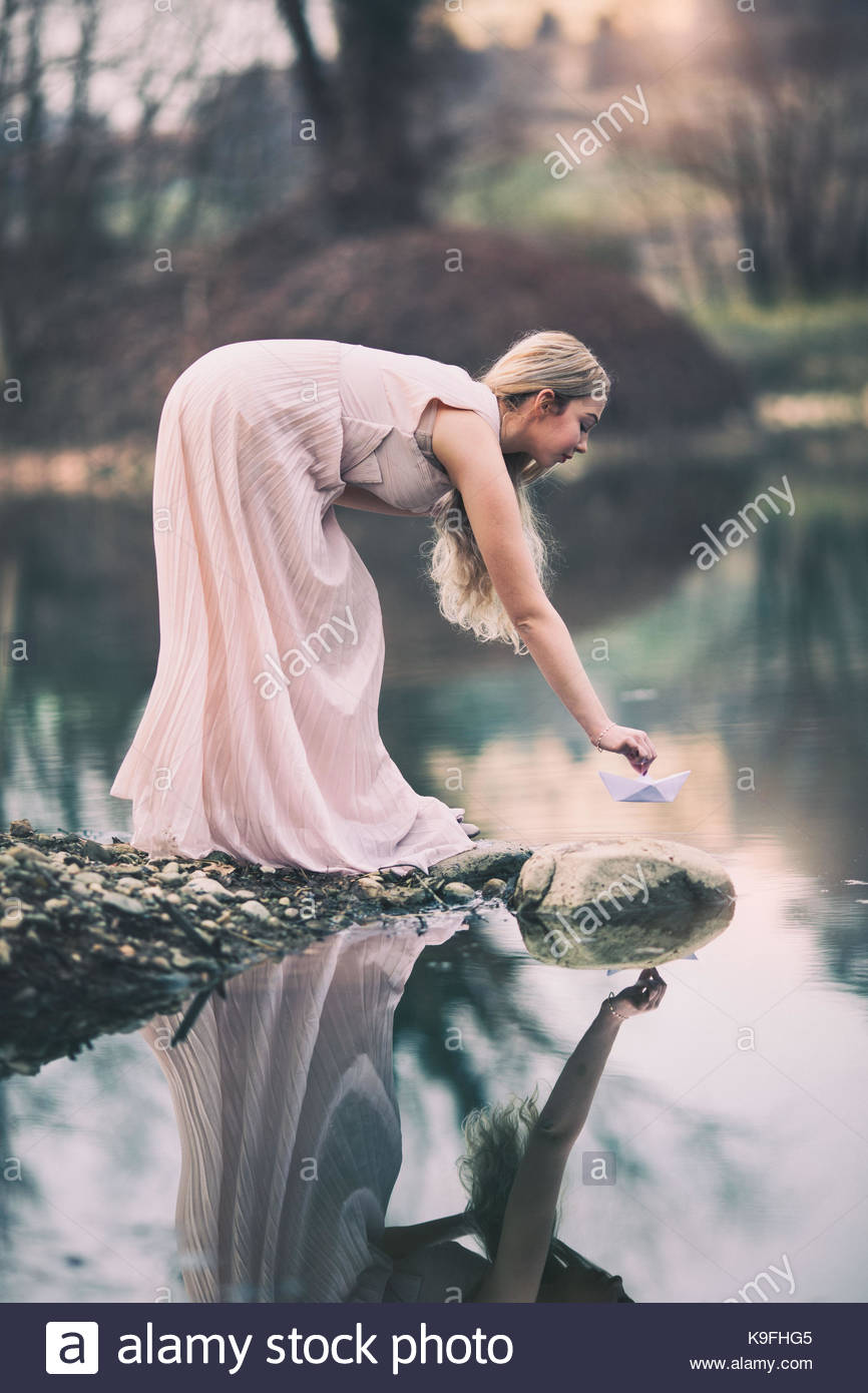 Lady in pink dress by a pond: beauty in nature Stock Photo