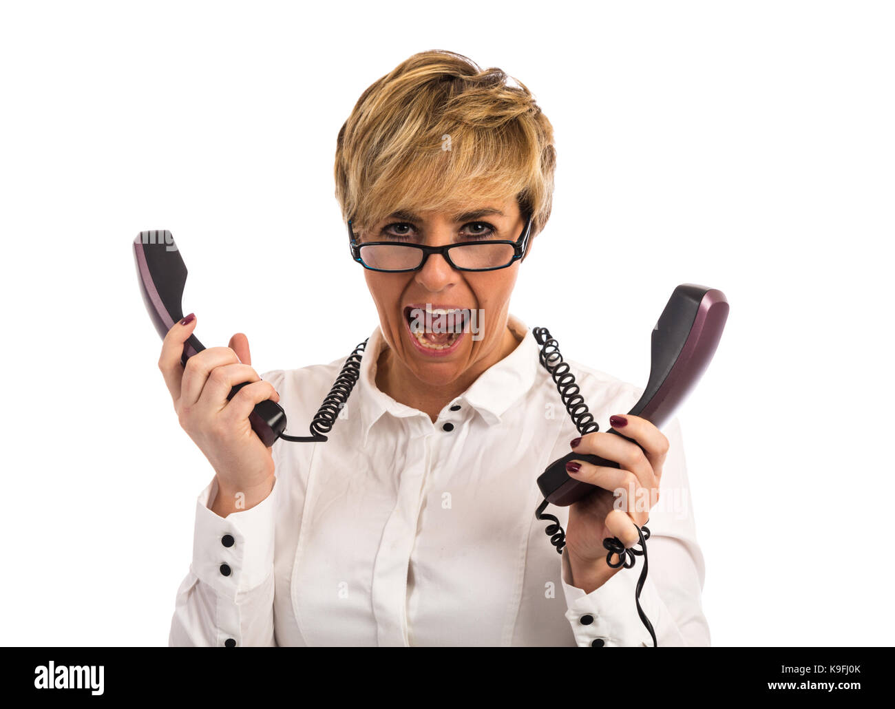 An overworked business woman struggles with too many phones - Stock Image