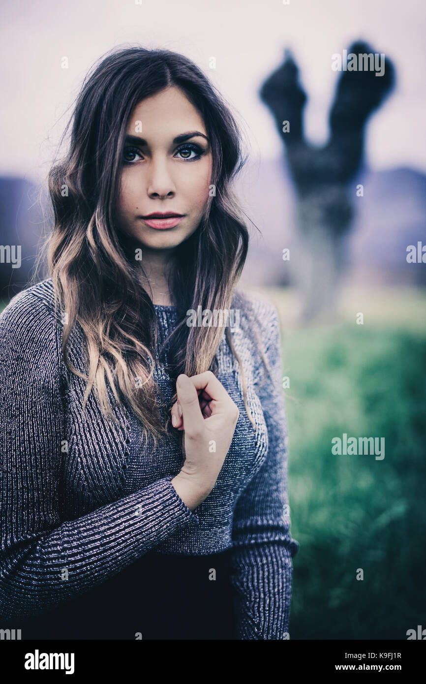 Portrait of a girl in a meadow, tree in the background. Vivid colors, green grass, purple mountains. Long wavy hair. - Stock Image