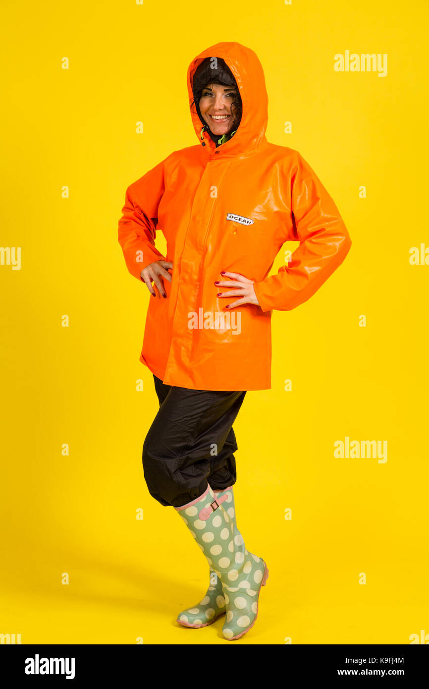 Young Woman Wearing Rain Gear On A Yellow Background Stock Photo Alamy