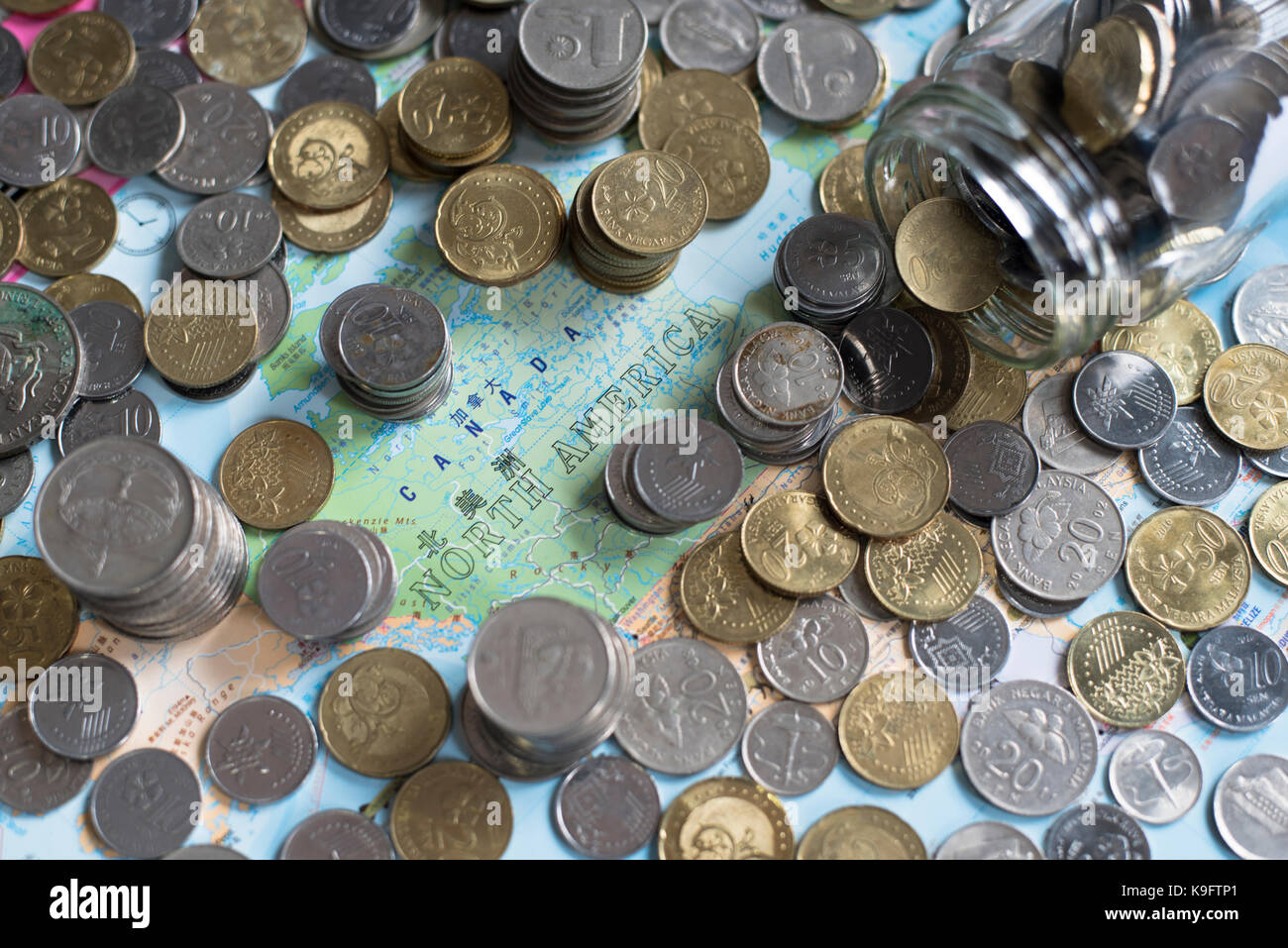 coins and glass jar on a map of 'North America'. Saving money for travel. saving concept and travel concept. - Stock Image