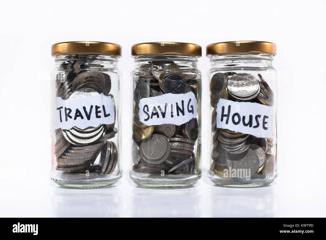 coins in a jar isolated on white background.saving concept. saving for travel,future and home/house - Stock Image