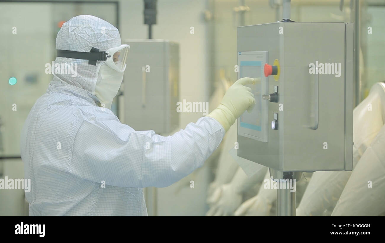 Pharmaceutical Production Line Worker at Work. Robotic arm lifting ampules at packaging line in pharmaceutical factory. - Stock Image