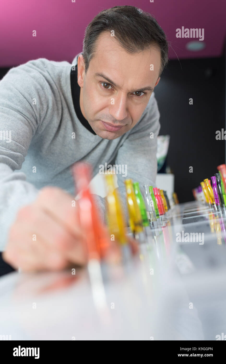 man displaying colorful e-cigarette refilling liquid containers - Stock Image