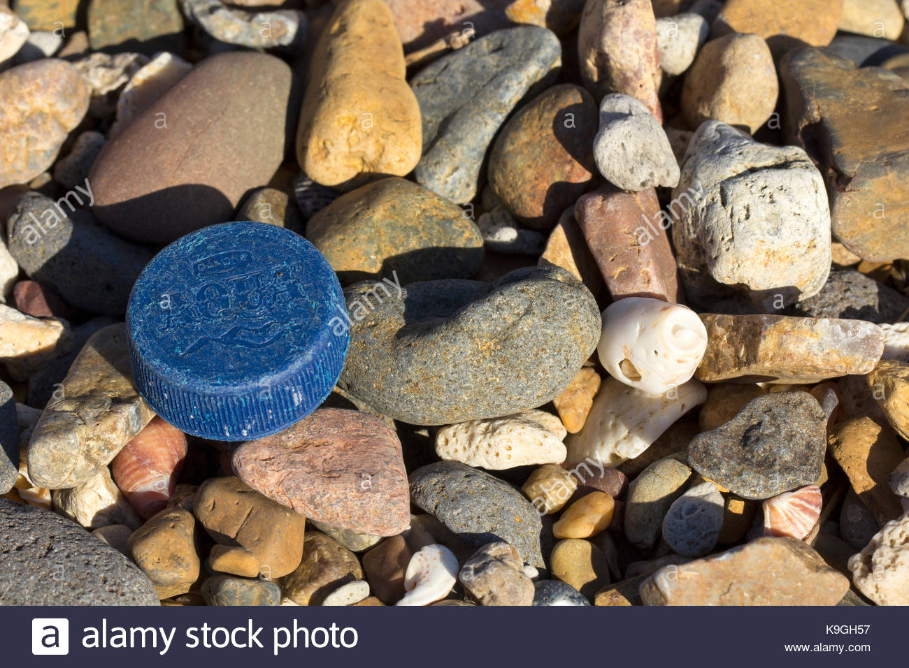 A cap from a single use bottle of water washed ashore and mixed with pebbles in Queensland, Australia. - Stock Image