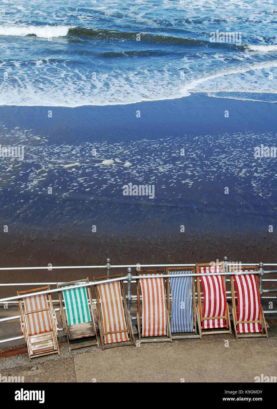 Several folded wood frame deckchairs secured to the railings of a promenade - Stock Image