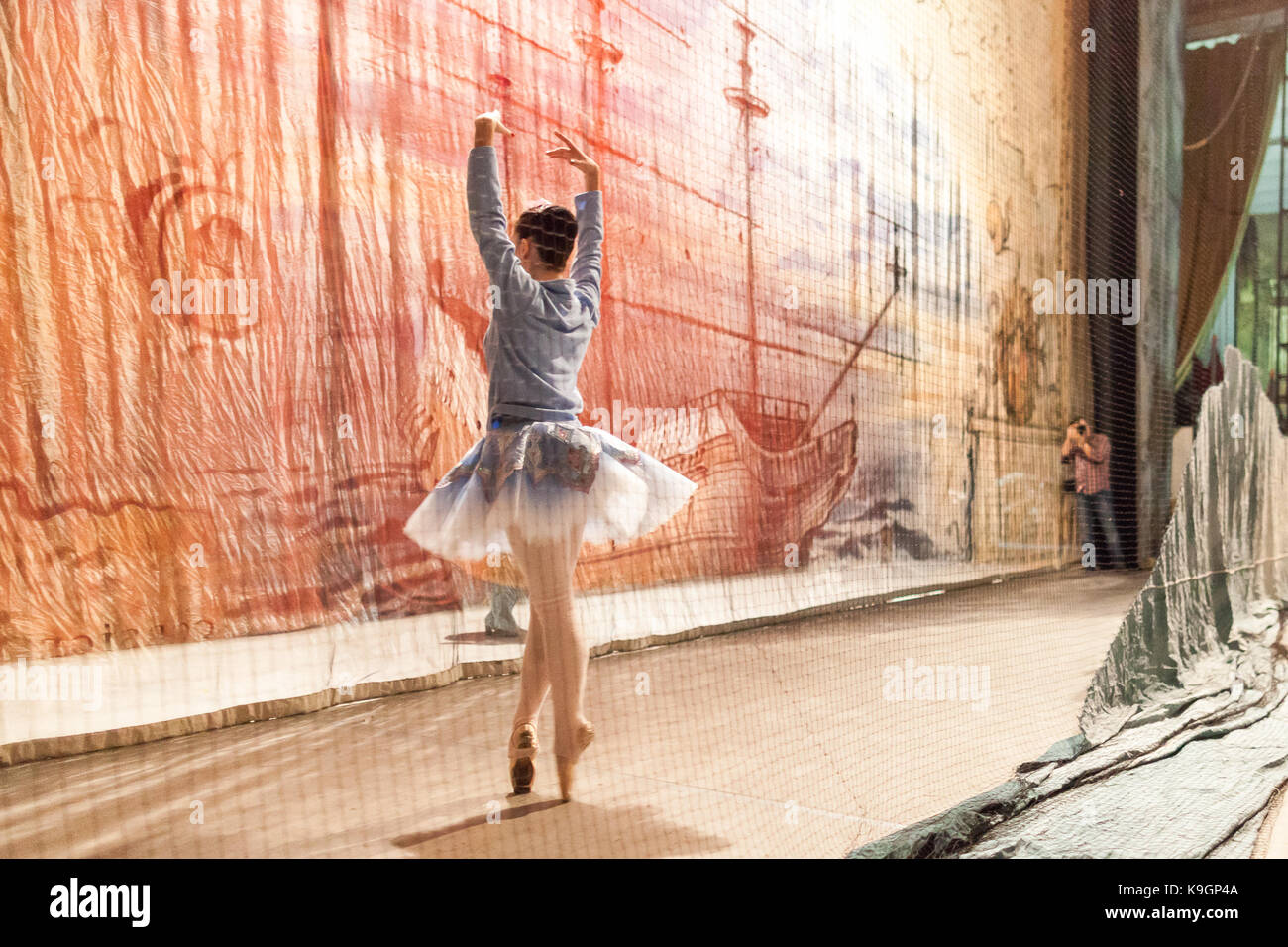 decoration, backstage, theater. man with camera taking photos of magnificent ballerina wearing for rehearsal in - Stock Image