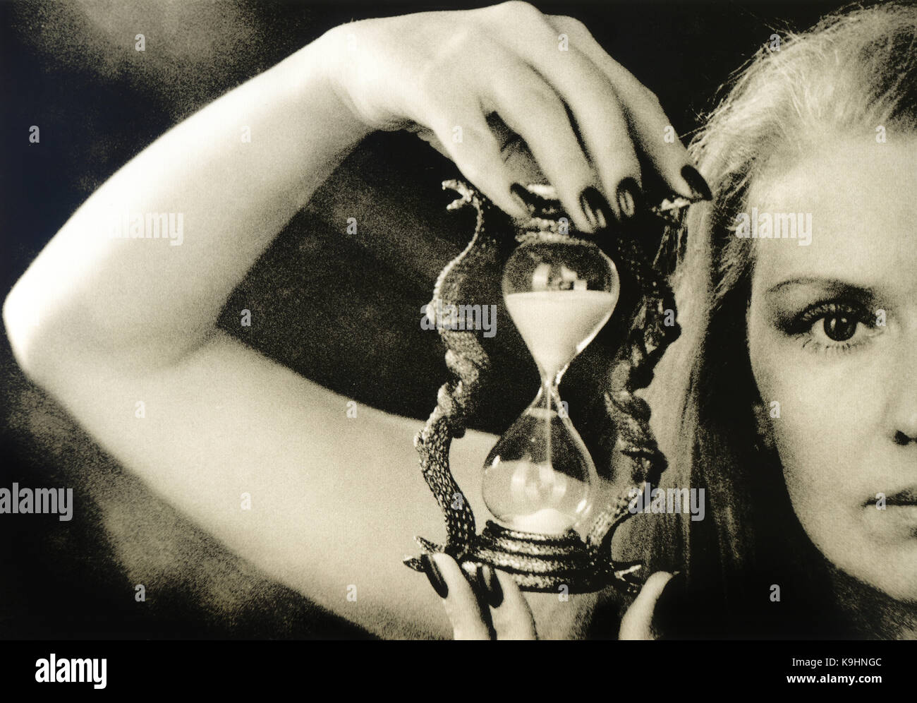A beautiful girl is holding an hourglass. Attention! The photo was made using the technology of lithographic printing. - Stock Image