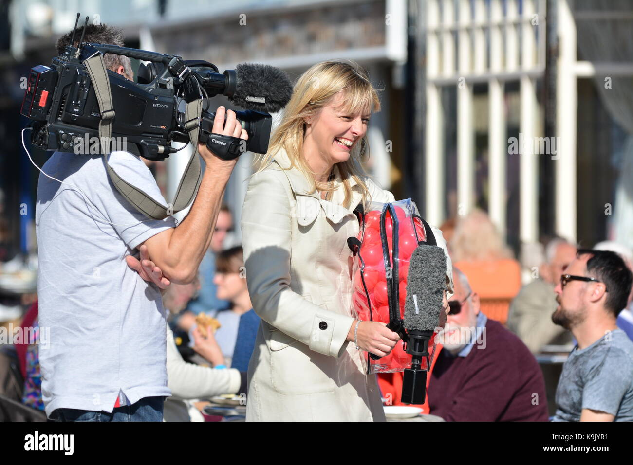 Outside broadcast on a hot day showing a pretty female reporter laughing while conducting an interview, being filmed - Stock Image