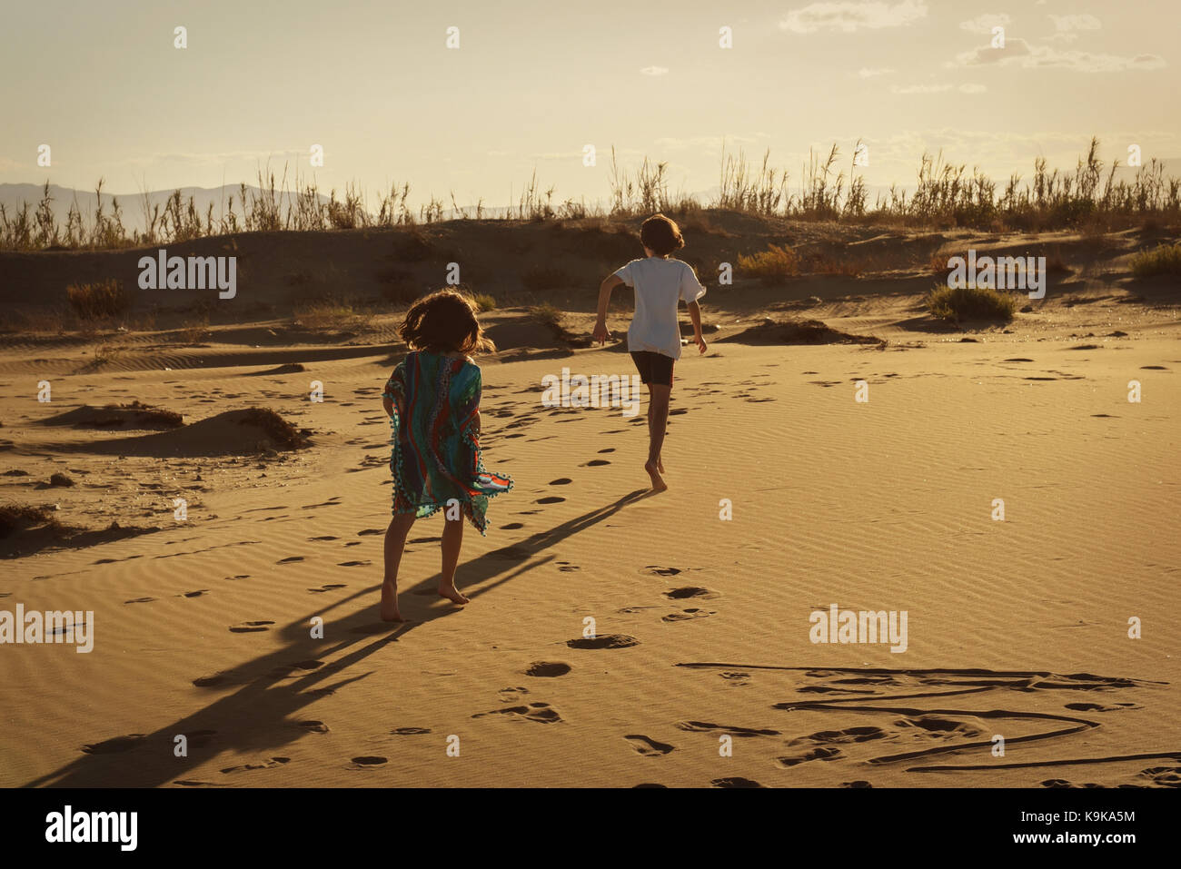 Boy and girl running wild on a sandy beach at sunset leaving footprints - Stock Image