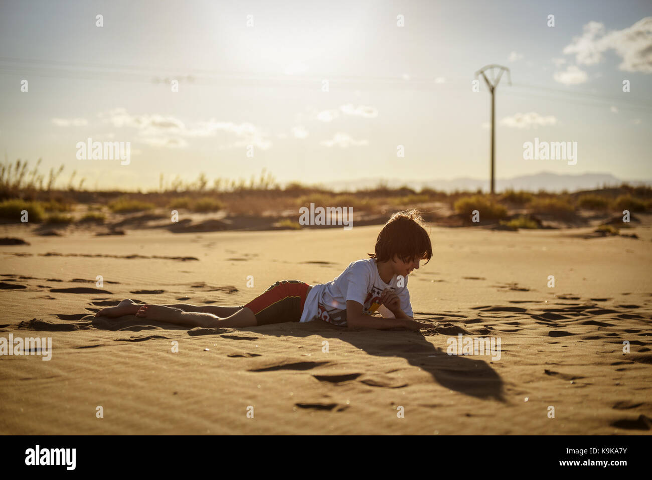 Relaxed boy in the sand at sunset - Stock Image