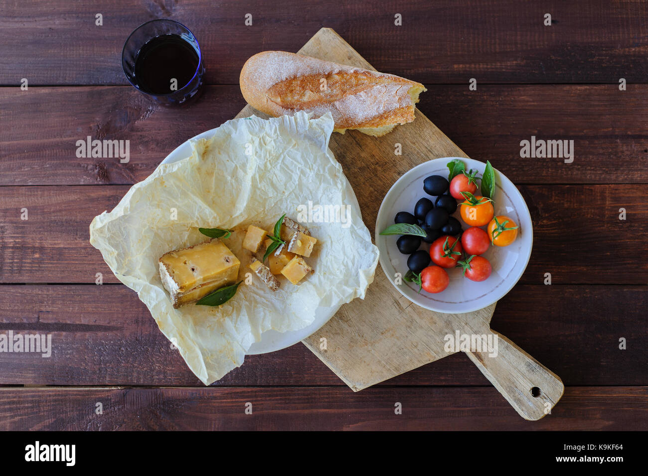 Piece of blue cheese, olives, and tomatoes close up - Stock Image