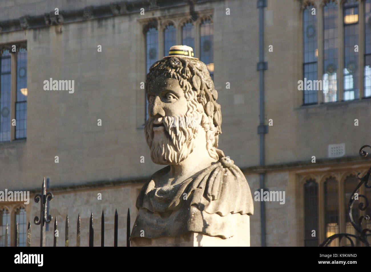 "One of the heads or ""Emperors"" outside the Sheldonian Theatre, Oxford. Decorated with a boater hat for freshers' Stock Photo"