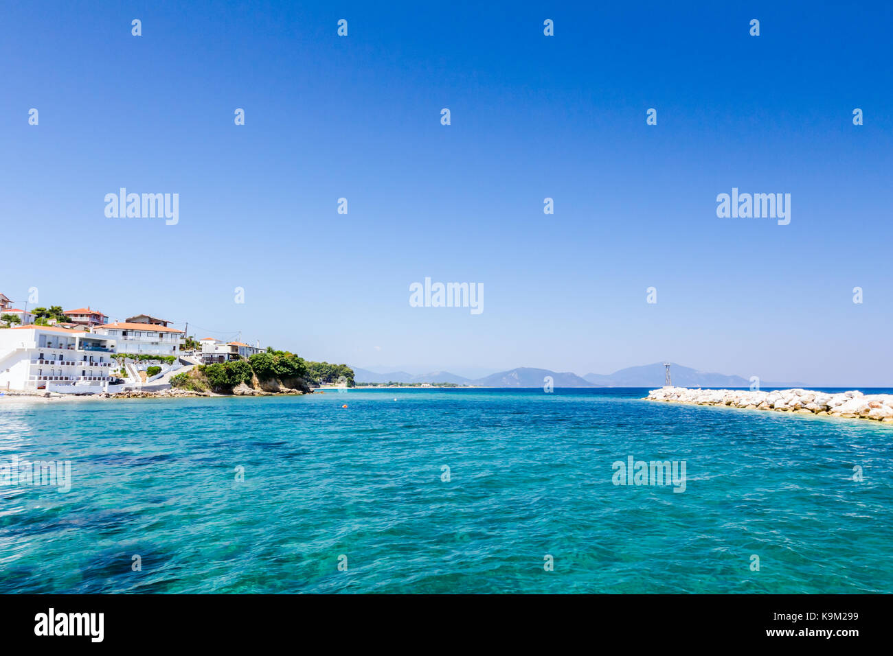 Rocky shallows with crystal clear water and beautiful settlement over blue sea. Stock Photo