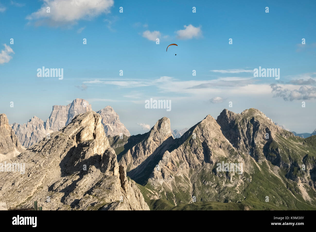 The Dolomites, Northern Italy. A paraglider soars above the tower of Ra Gusela (2595m), seen from the mountain guesthouse Stock Photo