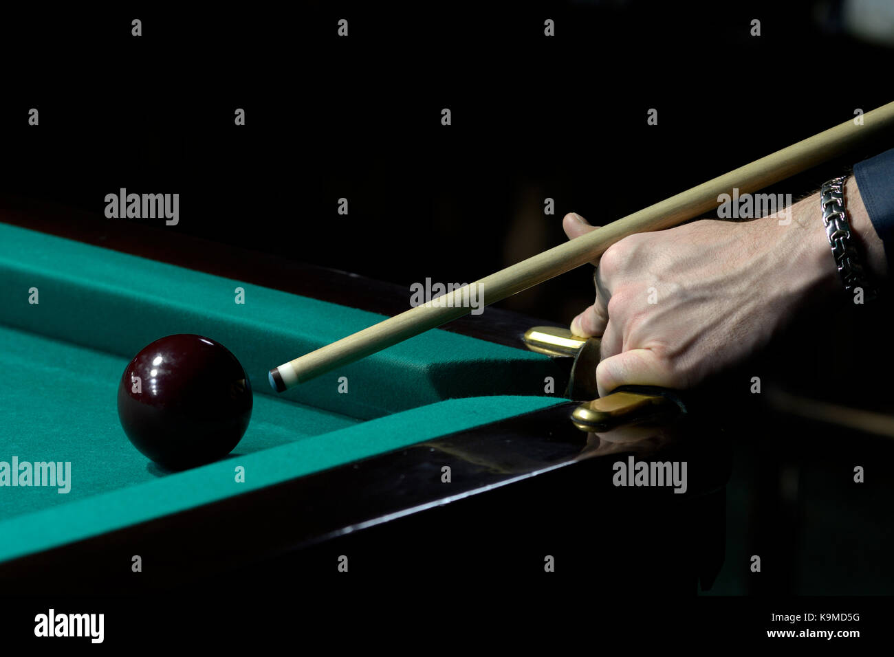 A player's arm with a cue on a pool table ready to stroke a ball - Stock Image