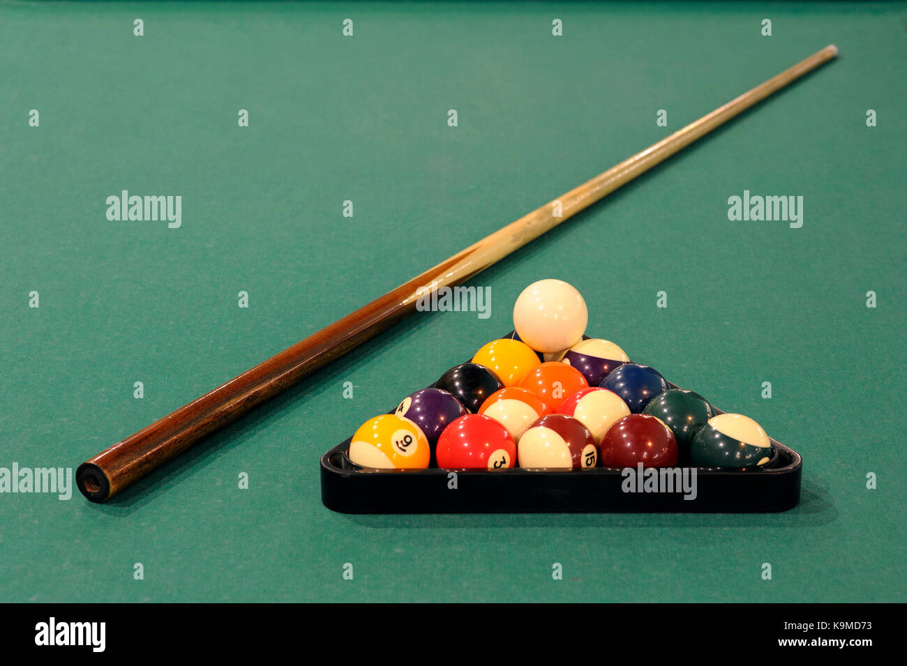 A cue stick and balls on a pool table - Stock Image