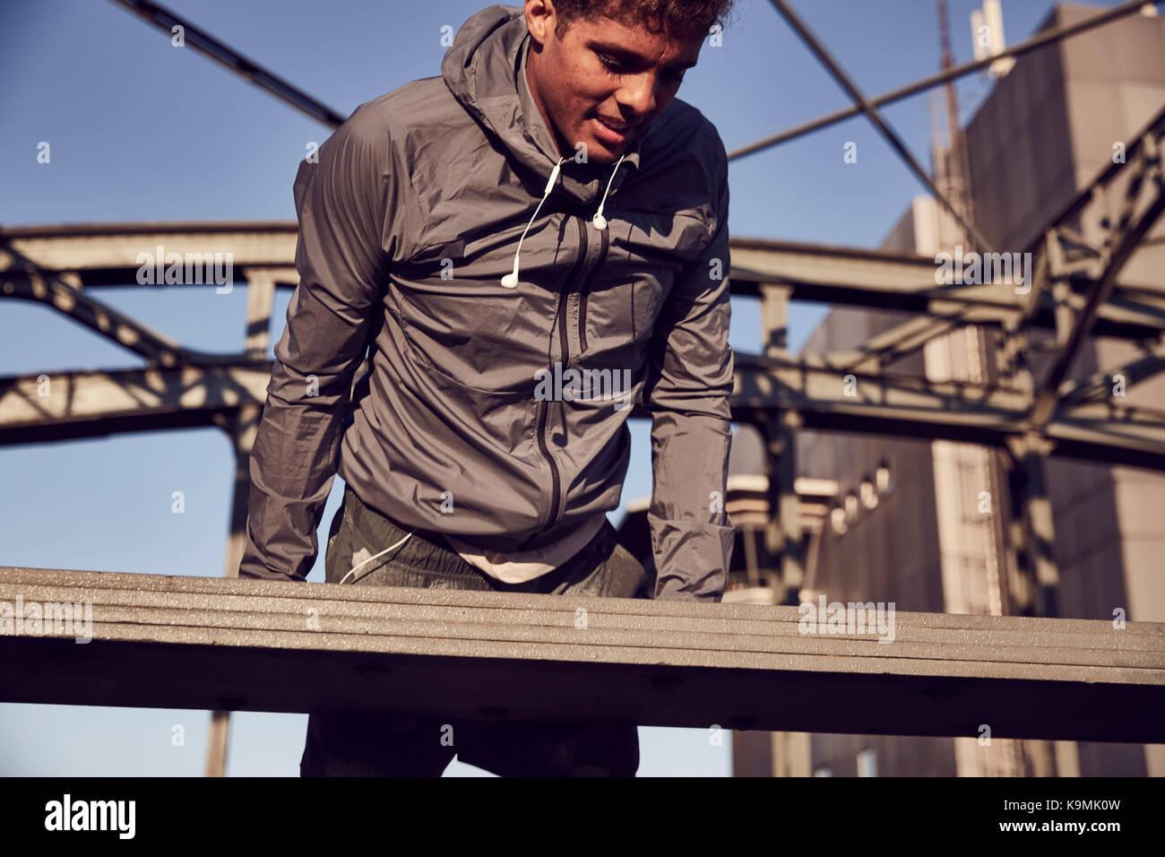 Germany, Munich, Young man training on a bridge - Stock Image