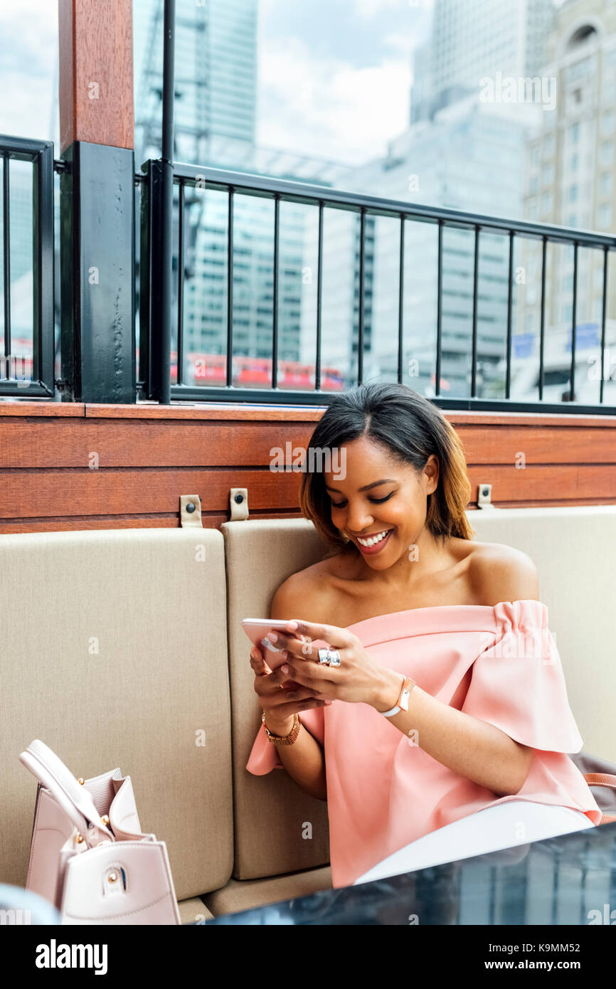 Smiling woman sending messages with her smartphone in the city Stock Photo