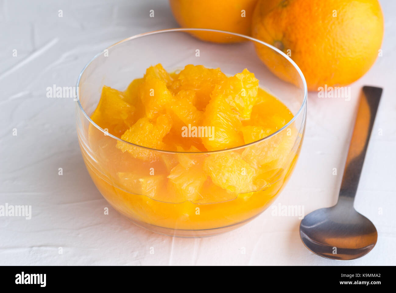 Fresh orange fruit slices with juice in glass dessert bowl on white rustic surface background and two whole oranges - Stock Image