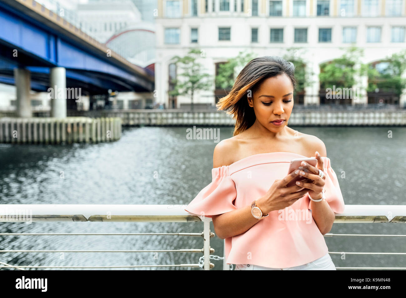 Woman sending messages with her smartphone in the city - Stock Image