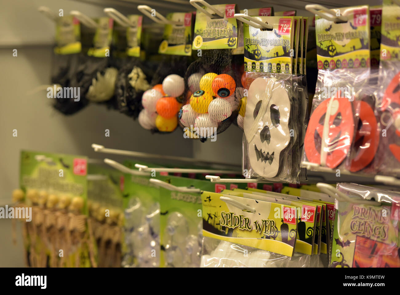 Halloween masks, toys and jokes for trick or treating on sale for sale in a retailing shopping on the high street - Stock Image