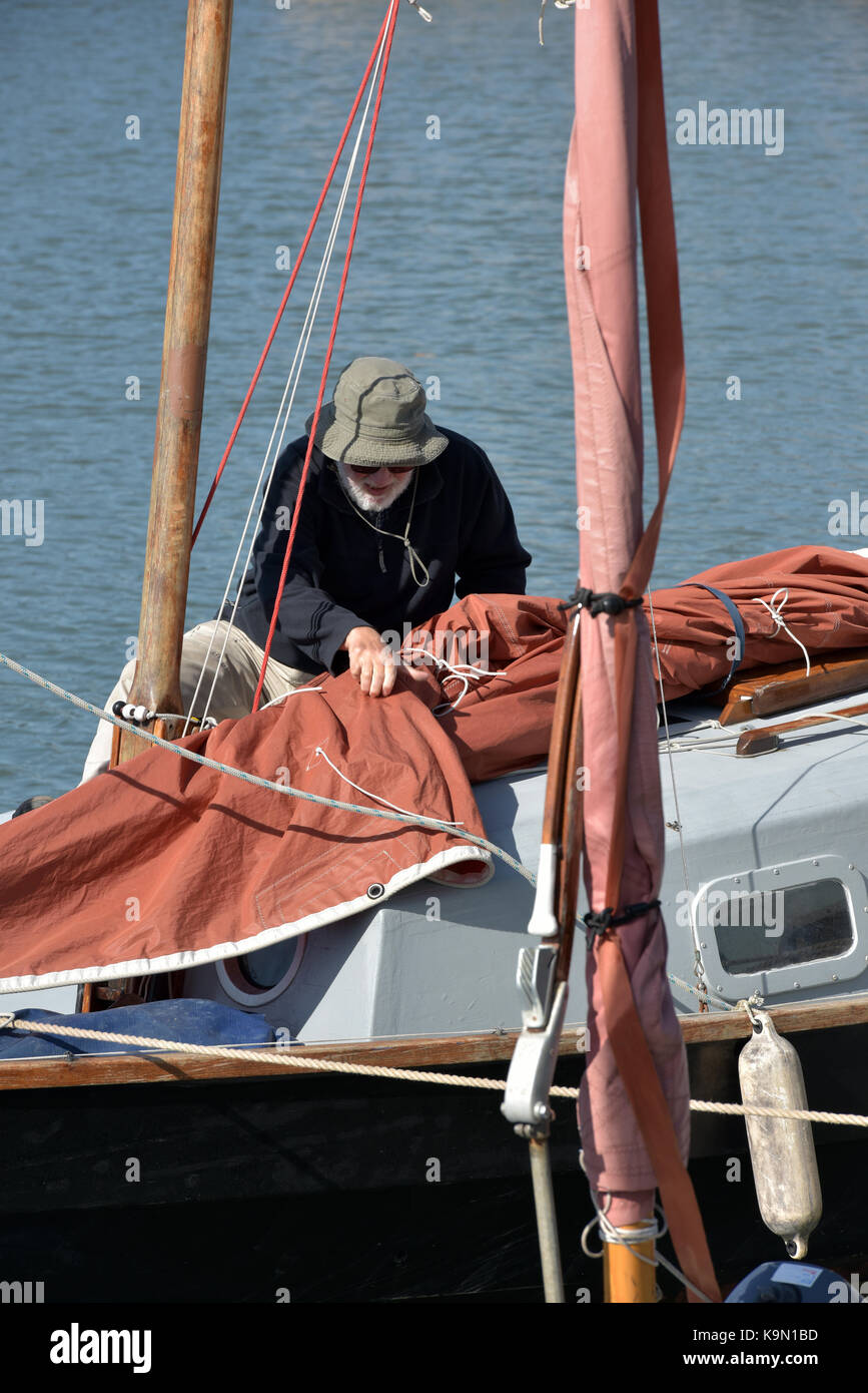a retired or middle aged man on a yacht sorting out his sails and tidying up the decks after going sailing or boating - Stock Image
