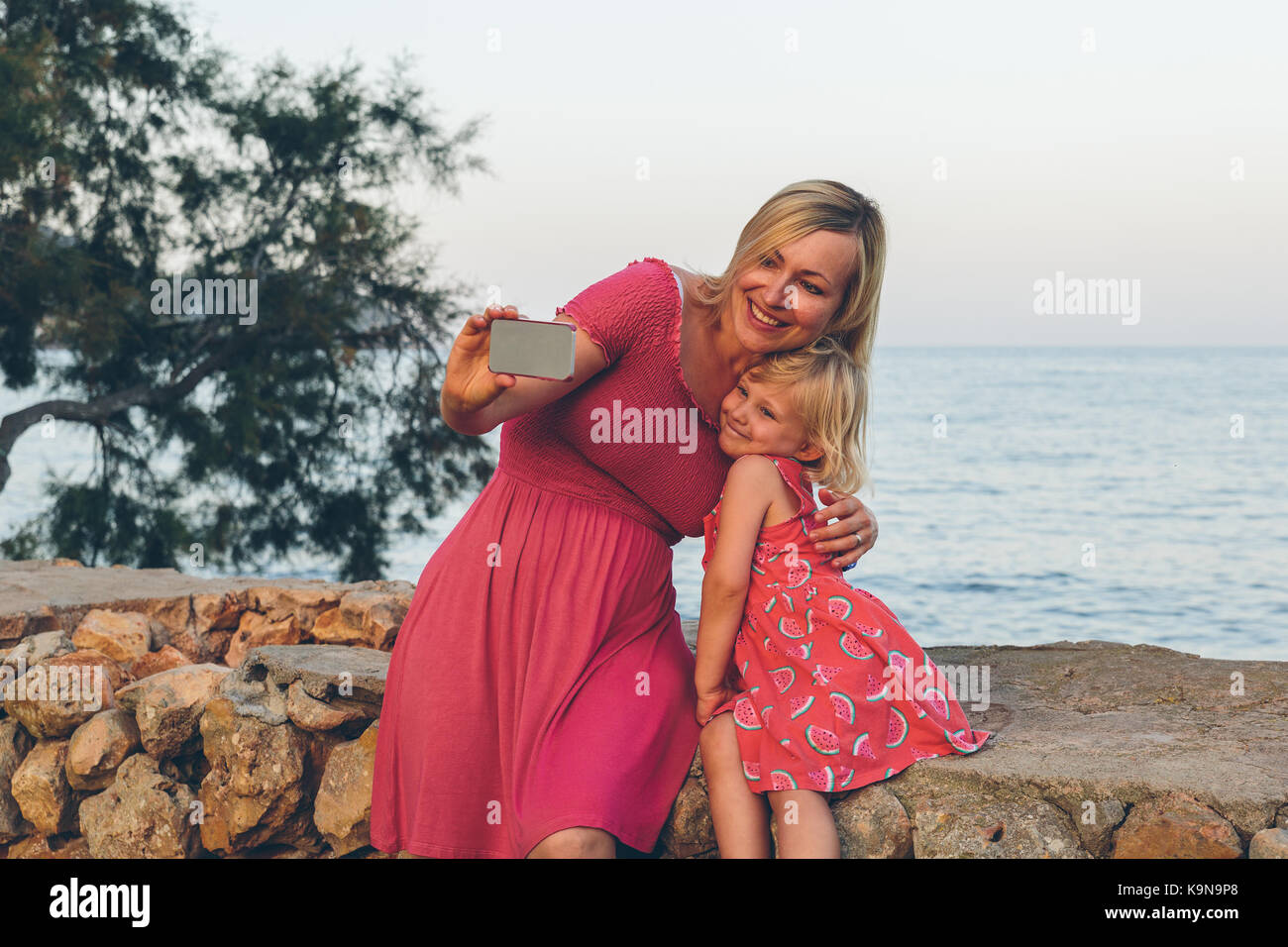 Mother and daughter taking a selfie with a mobile phone in front of the sea. - Stock Image