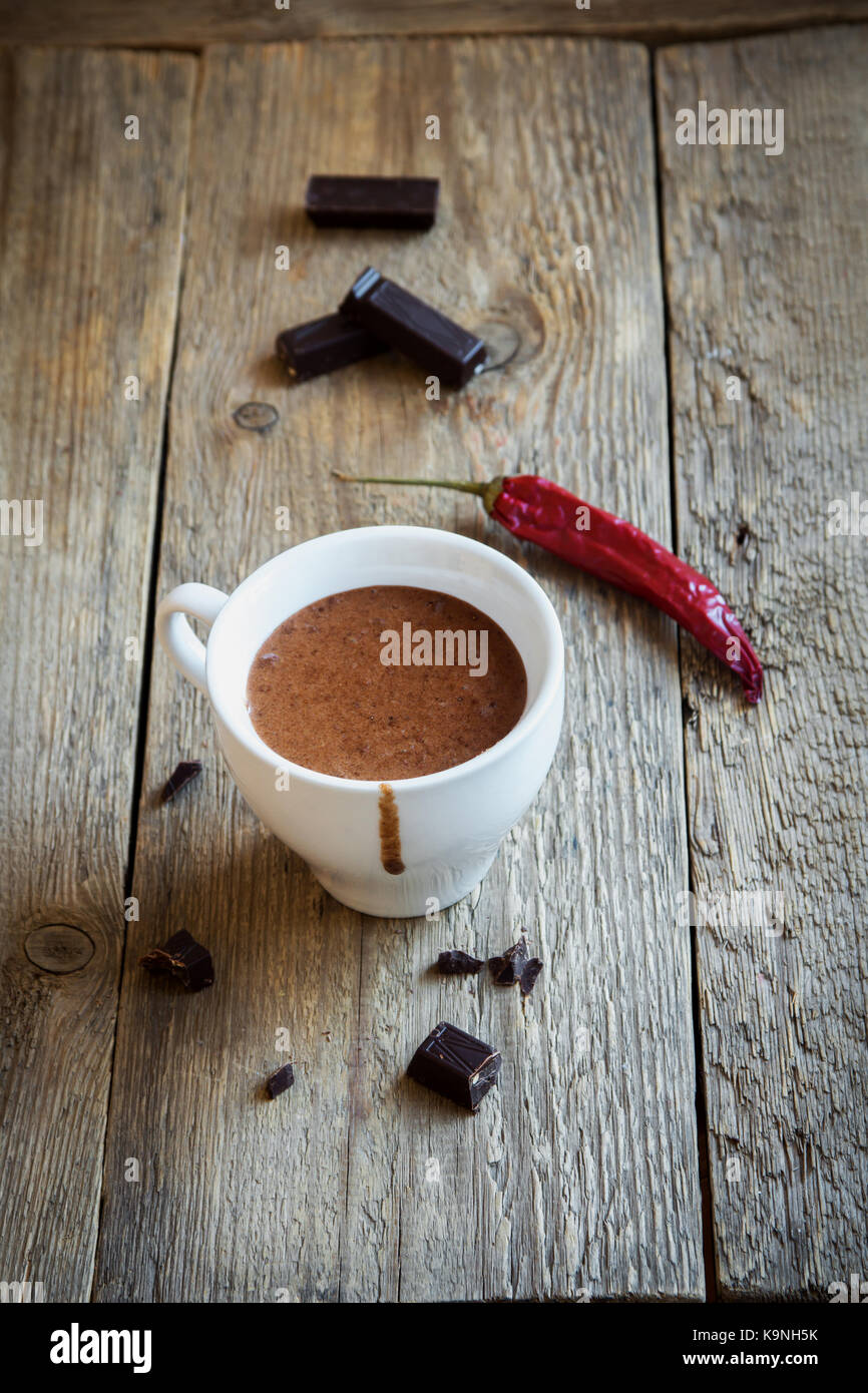 Hot Chocolate with chili pepper and chocolate pieces over rustic wooden background. Homemade Hot Chocolate Drink - Stock Image