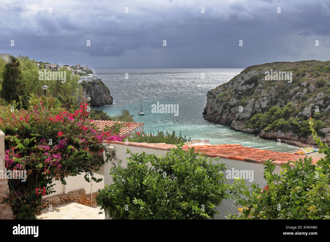 The Minorcan resort of Cala en Porter in the Mediterranean sea with stormy clouds - Stock Image