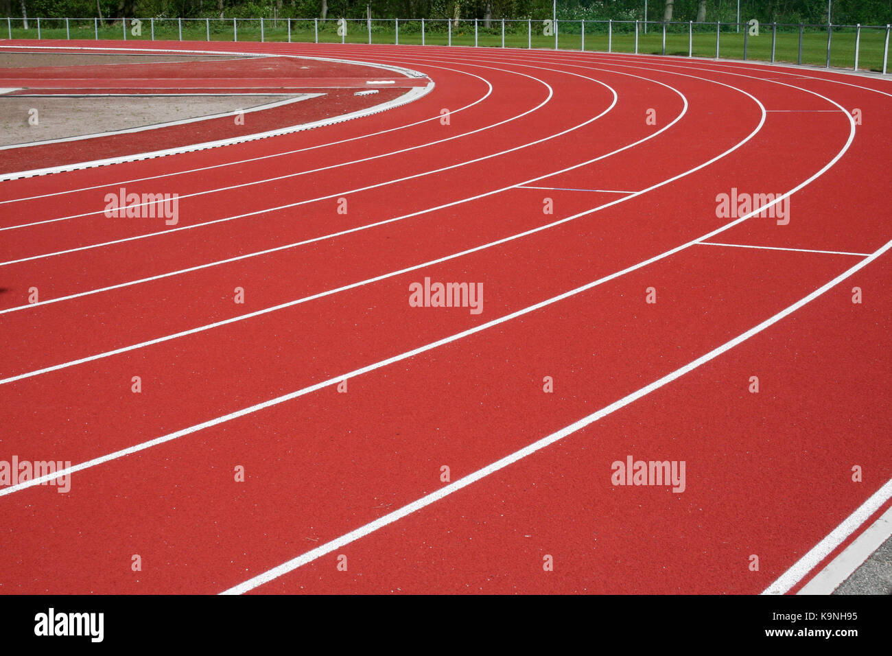 Bend of an empty athletics track in a green environment - Stock Image