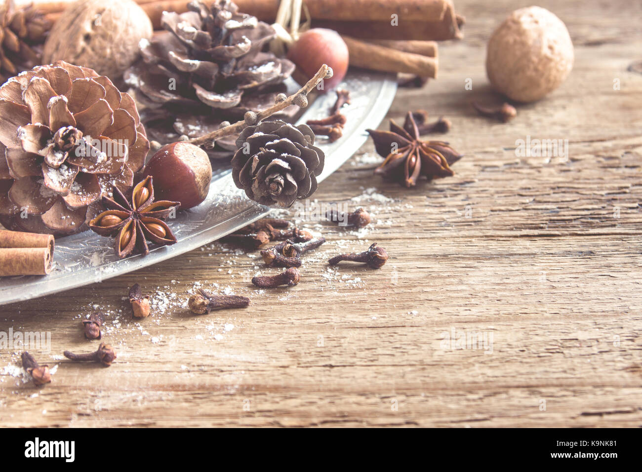 Christmas vintage decoration with cinnamon sticks and star anise, cones, nuts and Christmas ornaments over rustic - Stock Image