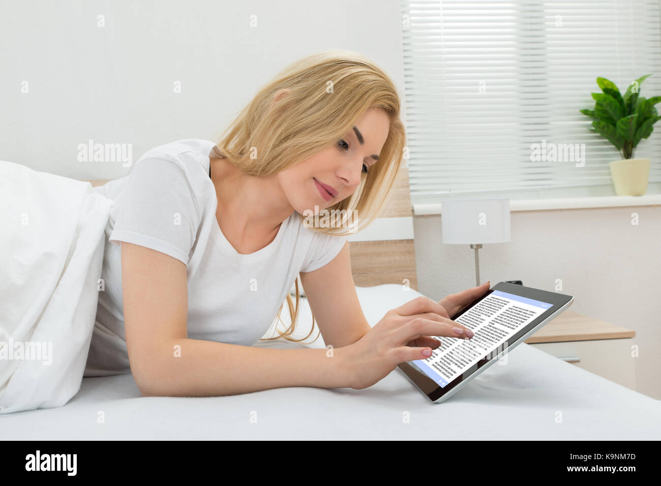 Young Woman Reading Ebook On Digital Tablet In Bedroom - Stock Image