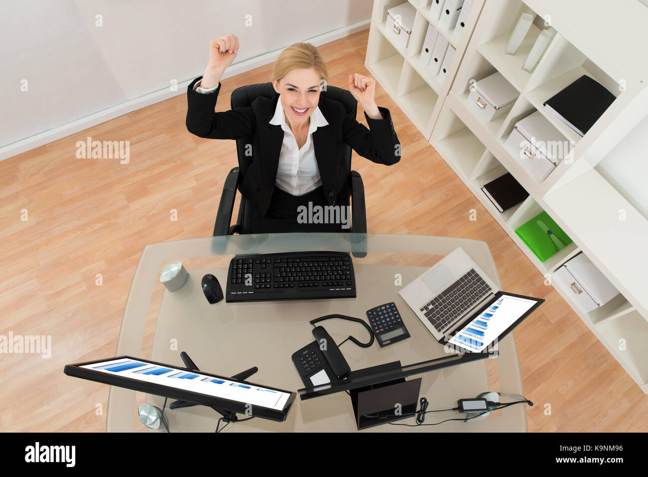 Young Happy Businesswoman Raising Arms In Office - Stock Image