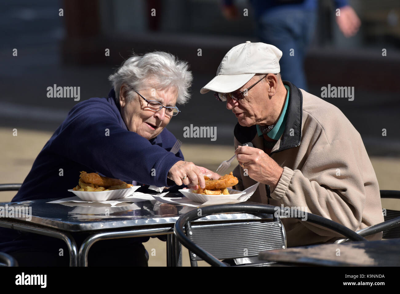 An elderly man and woman or man and wife eating fish and chips at a table outside alfresco dining with lady stealing - Stock Image