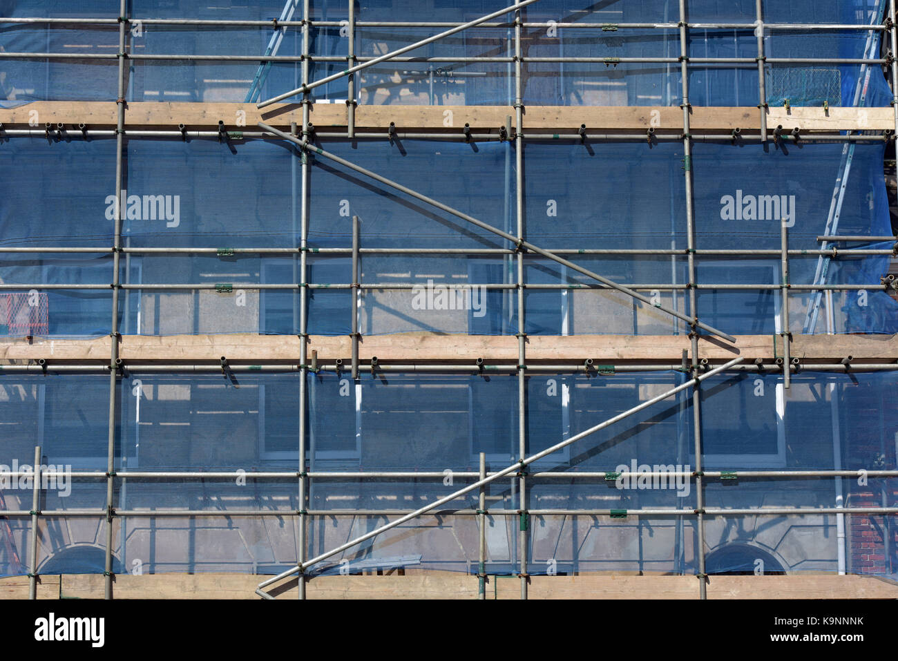 Some scaffolding erected on the front of a period building to allow access for works on restoration to be carried - Stock Image