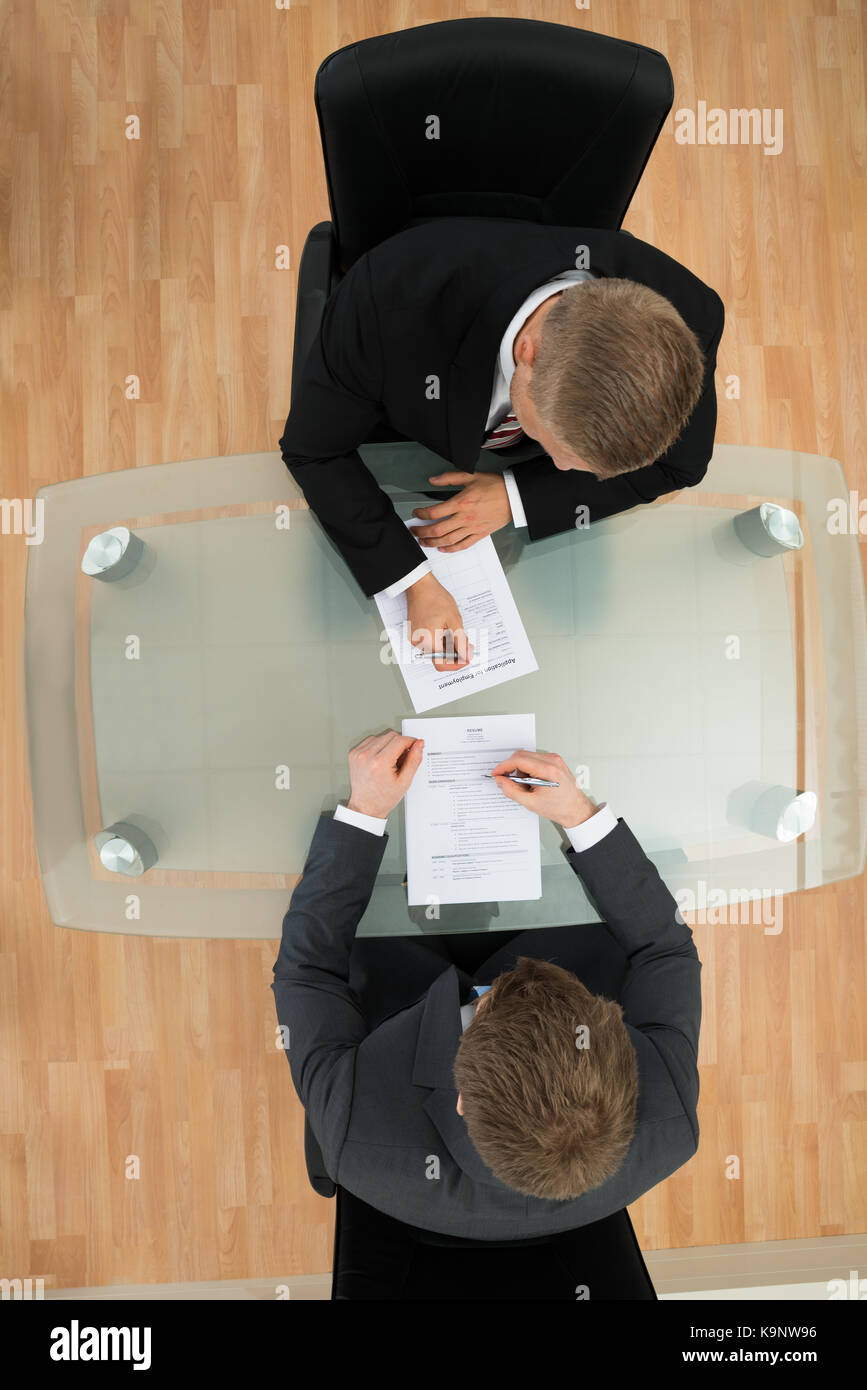 High Angle View Of Two Businessman Filling The Application Form - Stock Image