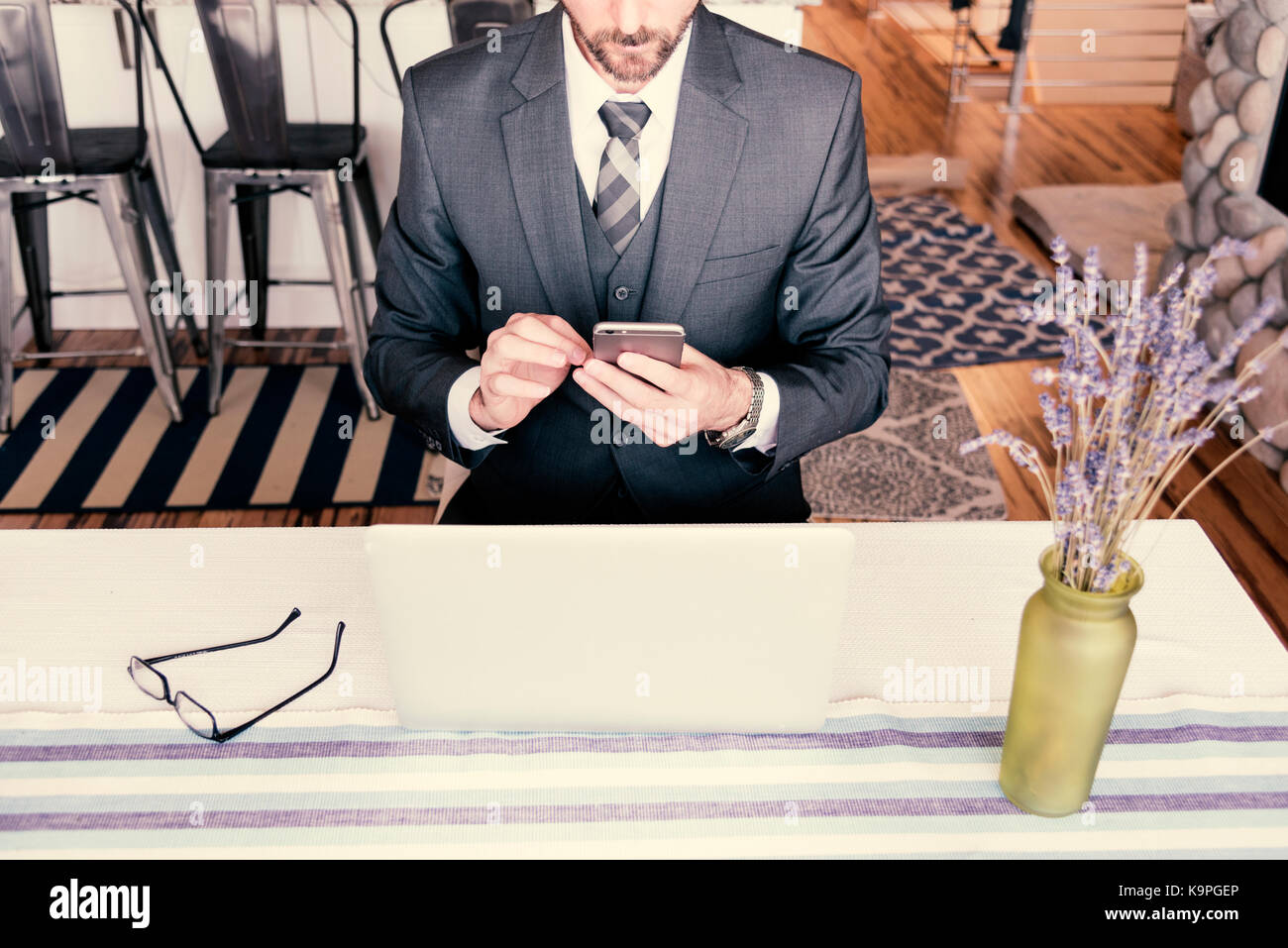 Man sitting at office table using a mobile phone to send a text message wearing a very nice suit with tie and vest. - Stock Image
