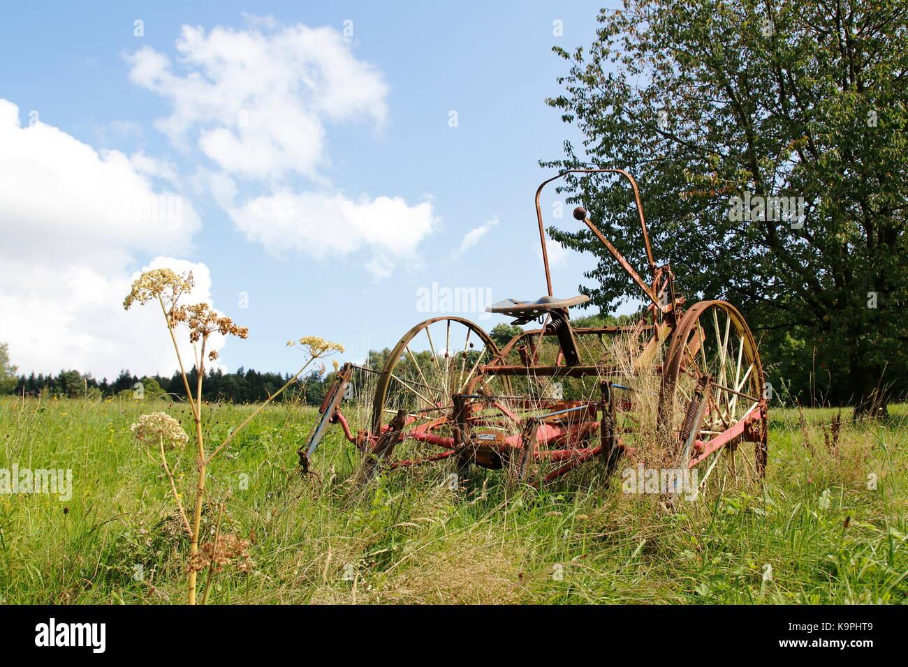 Alter, rostiger Traktor, Mähdrescher auf einer Wiese, einem Feld - Stock Image