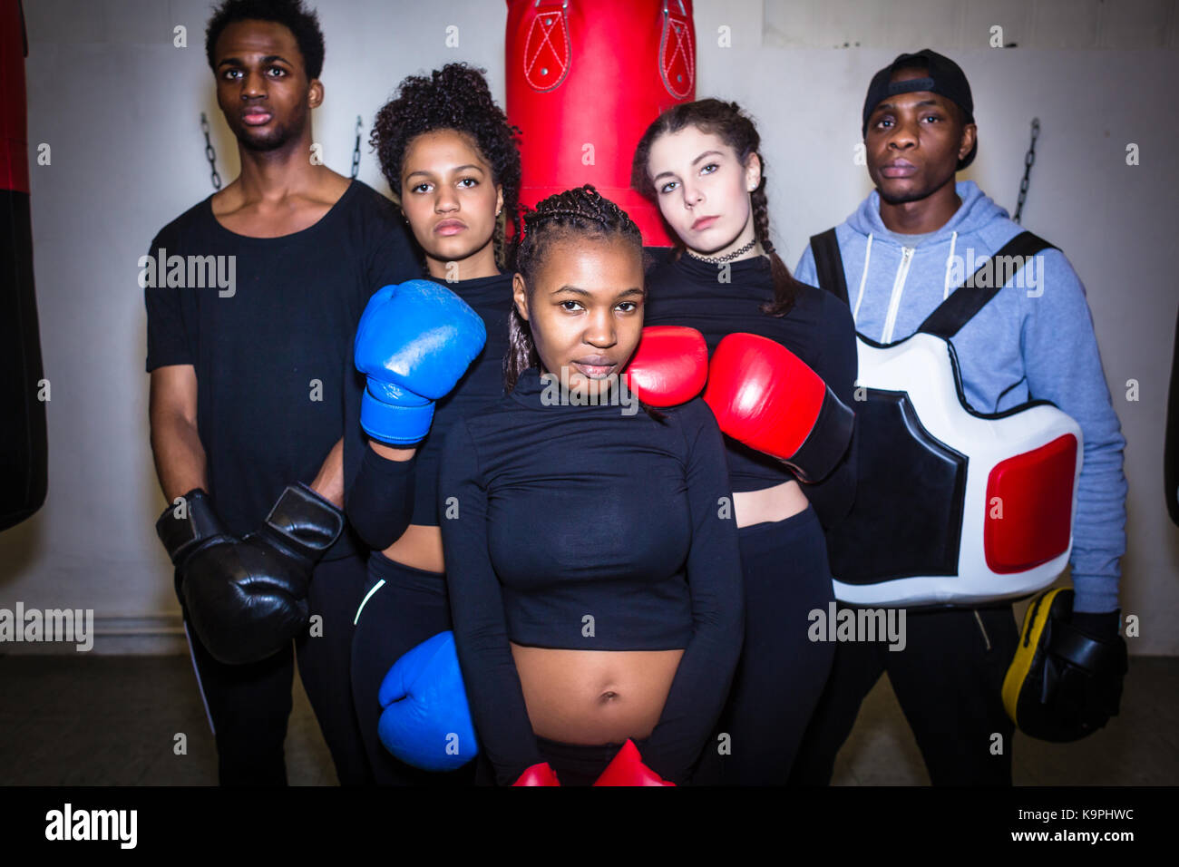 Portrait of four young determined boxers and their experienced b - Stock Image