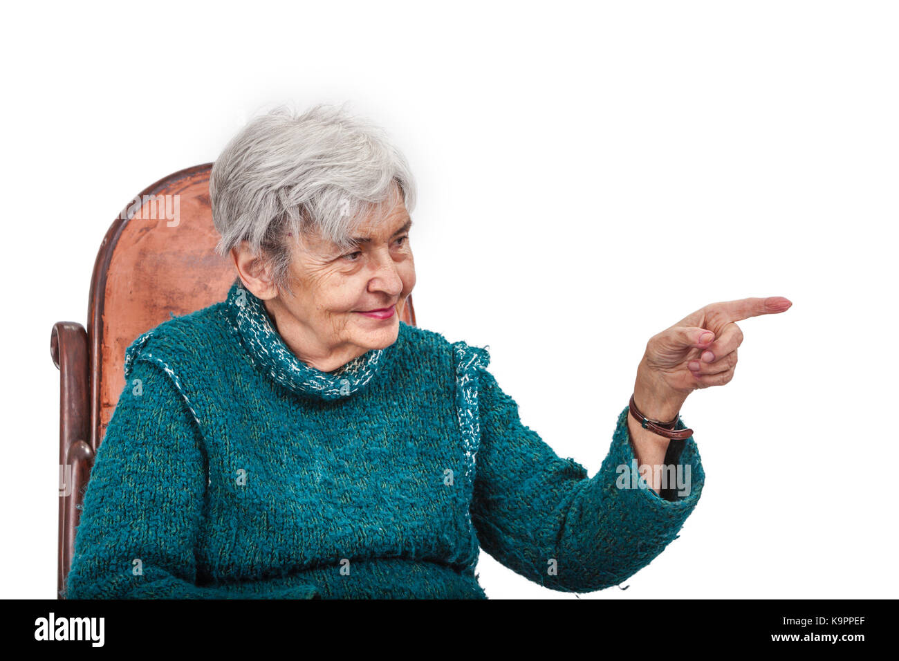 Old woman poiting her left finger to something and looking to it, isolated against a white background. - Stock Image