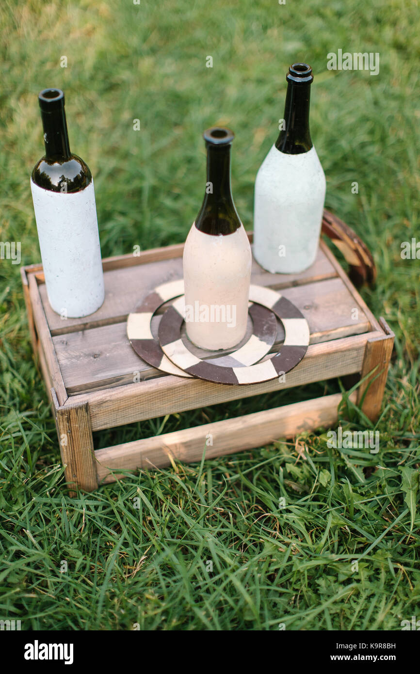 handcraft, summer, vacation concept. three wine and champagne bottles covered by half with white and light pink - Stock Image