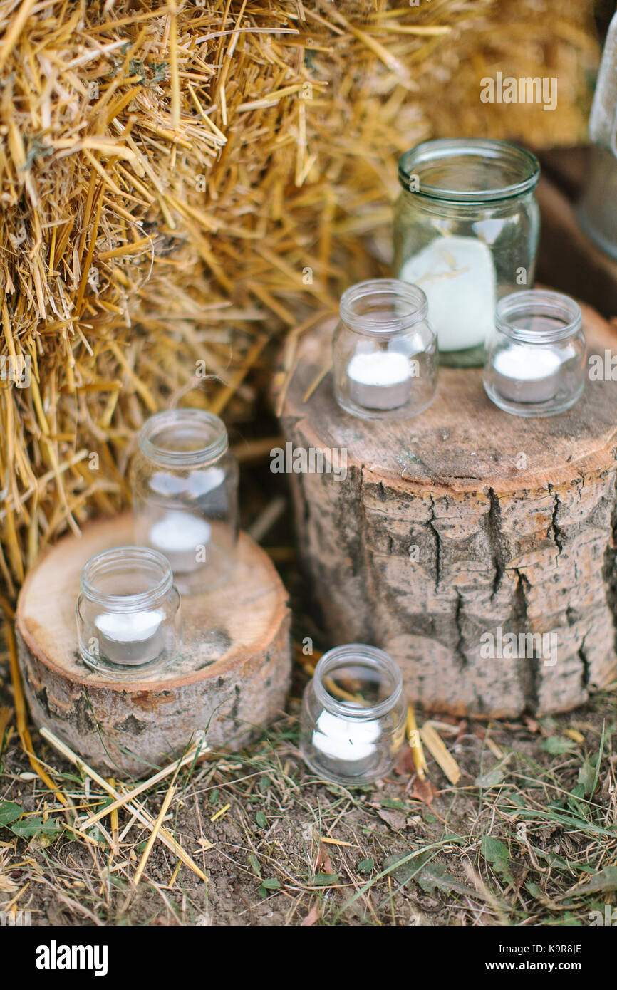 feast design, autumn, country style concept. sparkly glass jars of different sizes used as original candle holders - Stock Image