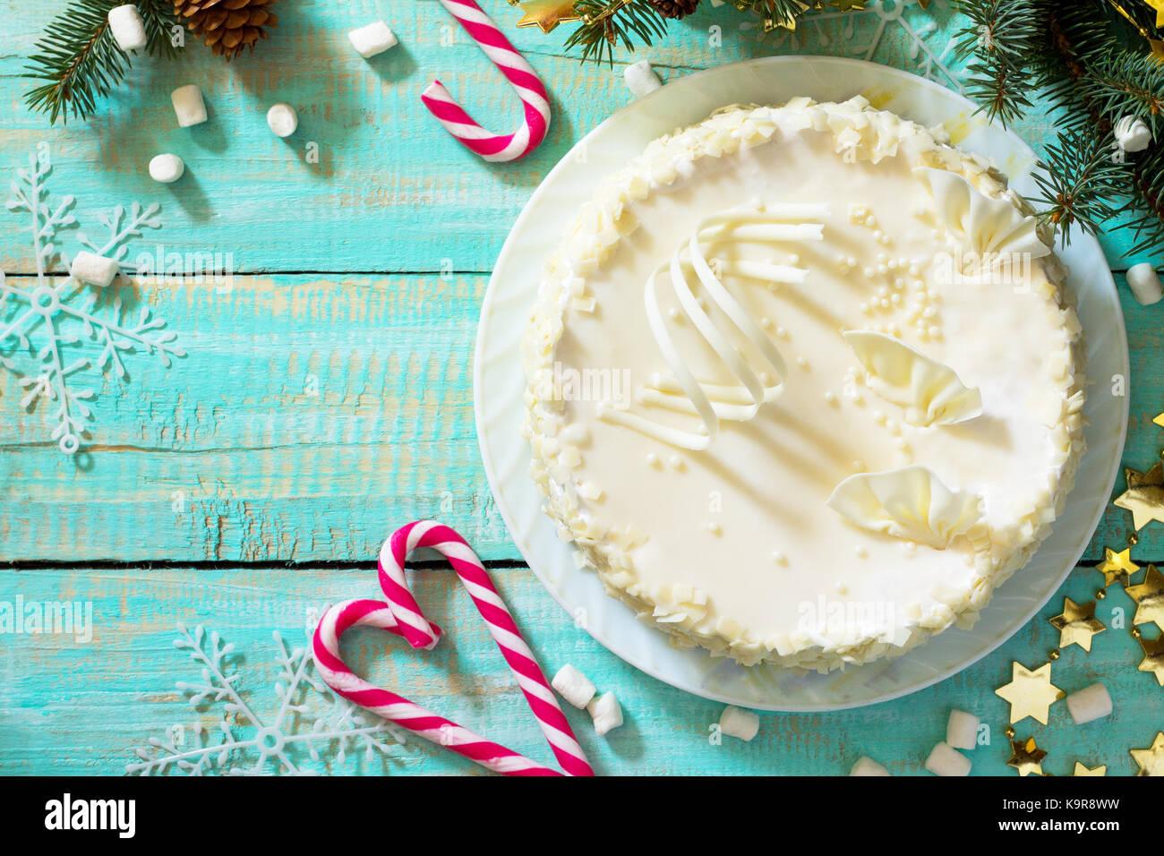 Holiday cake with icing white chocolate on festive christmas background. - Stock Image