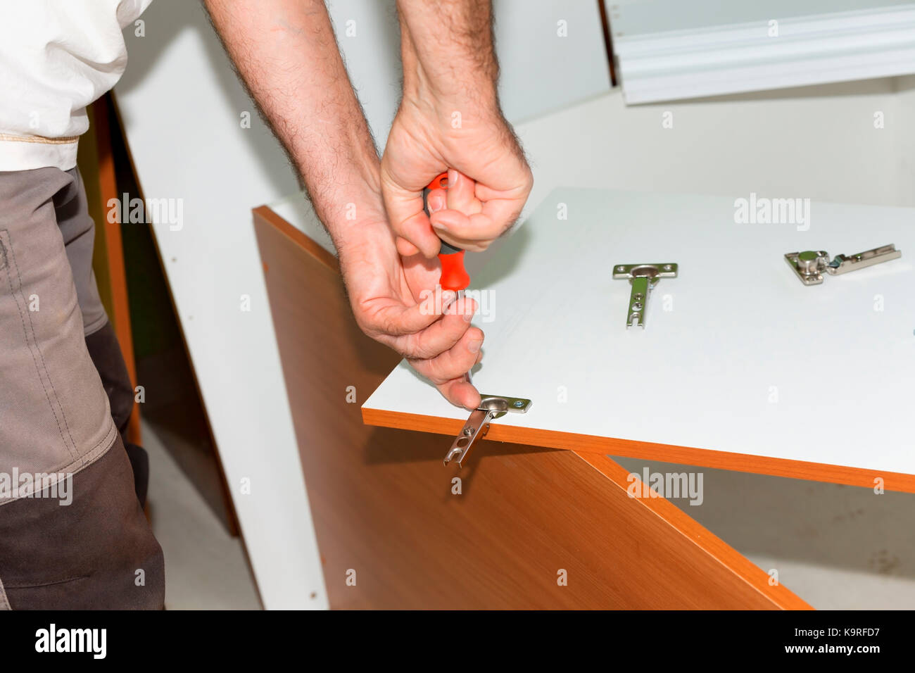 A person screws the hinges on a newly purchased wardrobe. - Stock Image
