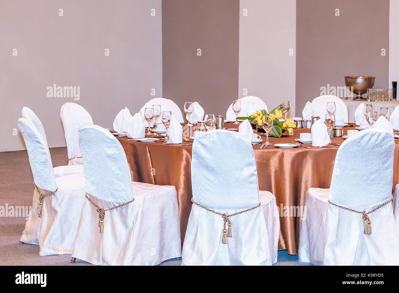 Charmant An Event Dinner Set Up With White Seat Covers And Bronze ...
