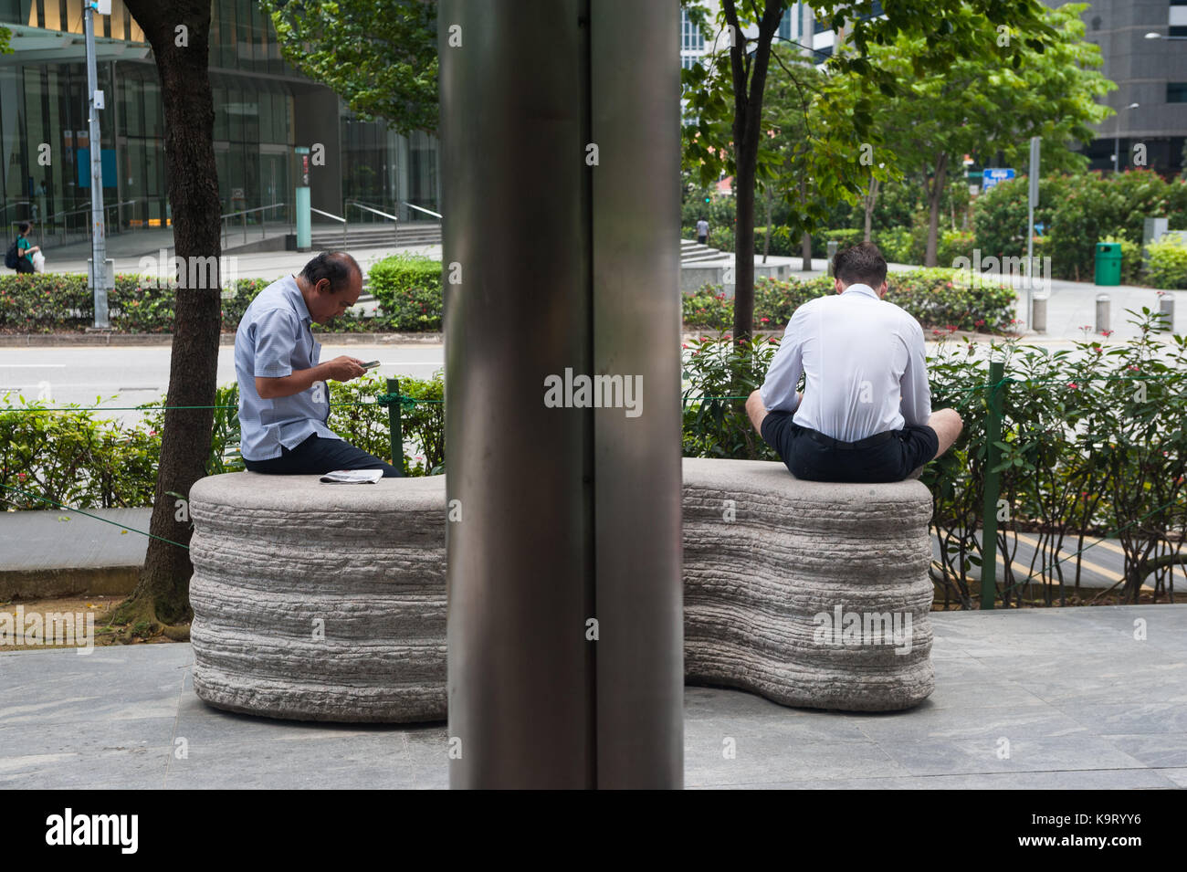 03.09.2017, Singapore, Republic of Singapore, Asia - Two men are occupied with their smartphones in Singapore's - Stock Image