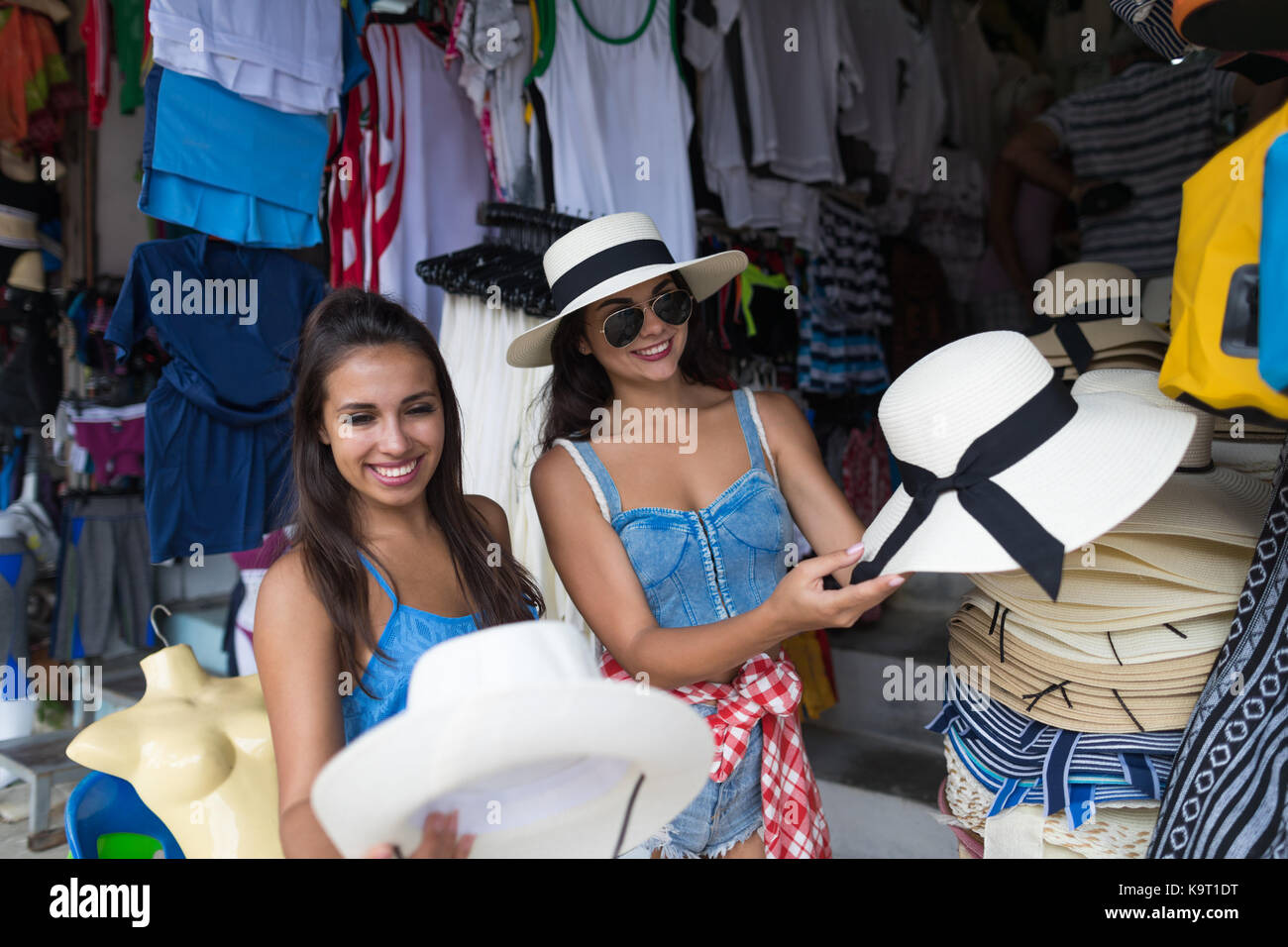 Two Women Tourists Buying Hat On Asian Open Street Market Of Clothes Young Female Shopping At Traditional Bazaar - Stock Image