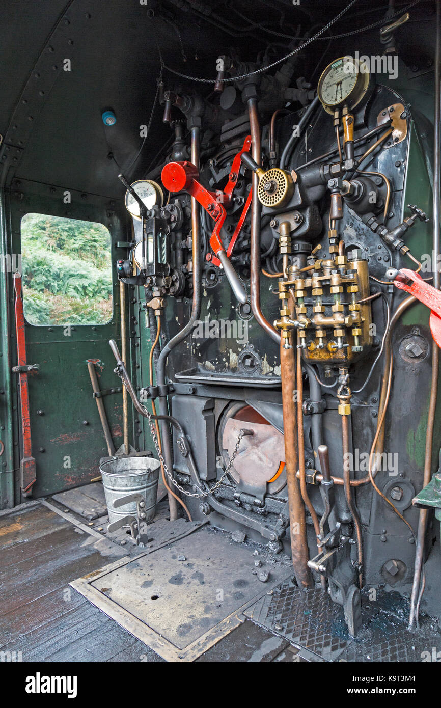 Footplate and cabin of a steam locomotive engine, showing dials, levers, pipes, and opening for coal to feed the - Stock Image